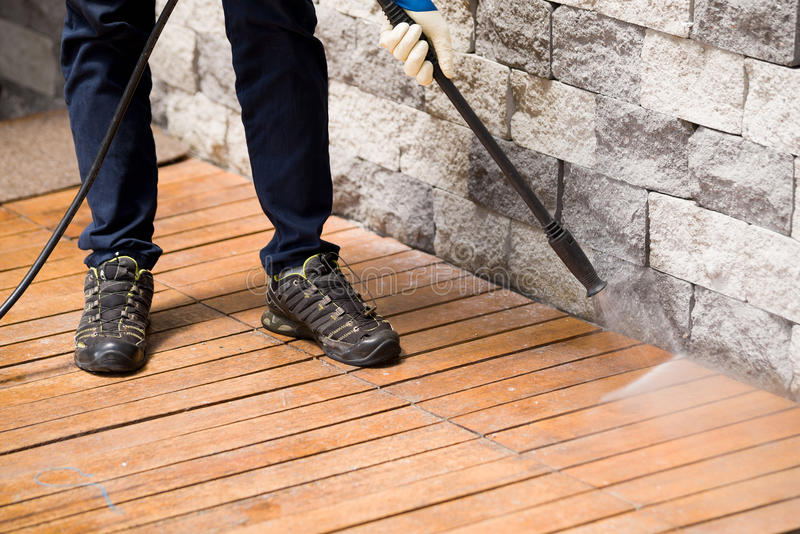 Close up of a man cleaning terrace with a power washer - high water pressure cleaner on wooden terrace surface royalty free stock image