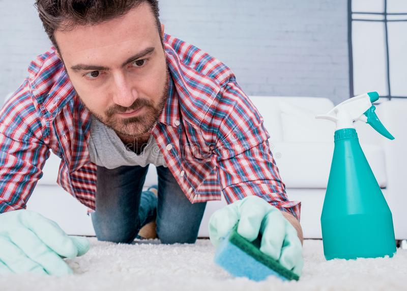 Close up man cleaning white carpet floor with sponge. Wiping wooden white carpet and floor with a sponge stock image