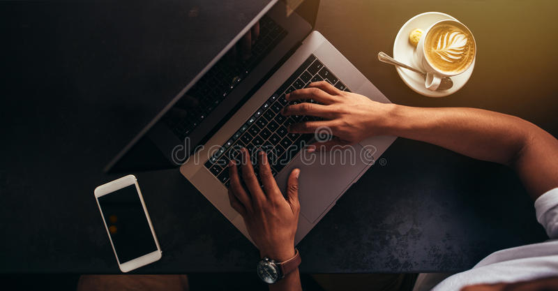 Close up of man at coffee shop working on laptop. Close up shot of young man sitting at coffee shop and working on laptop. Focus on hands typing on laptop royalty free stock image