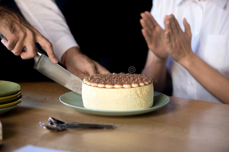 Close up of man cutting birthday cake in office. Close up of employee throwing birthday party in office, sitting at table cutting cream pie with knife, excited royalty free stock photo