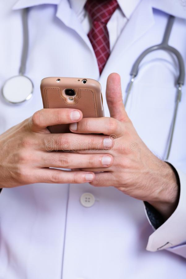 Close up of man doctor using mobile phone. Isolated against white background stock image