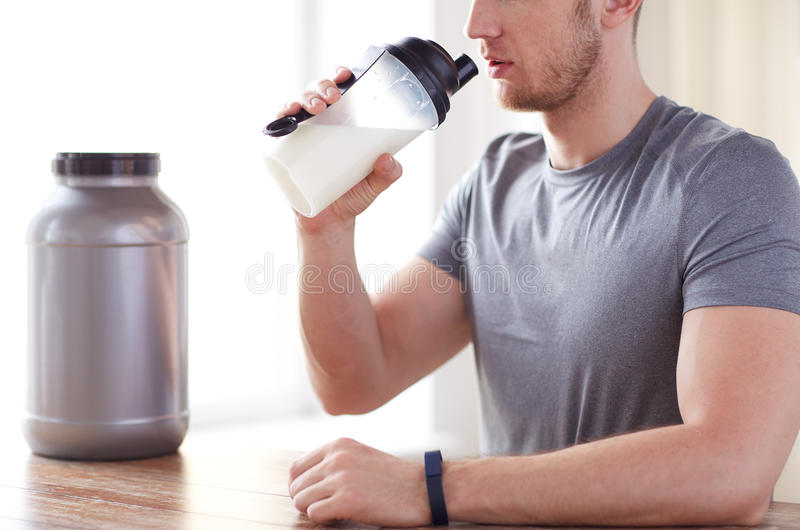 Close up of man drinking protein shake. Sport, fitness, healthy lifestyle and people concept - close up of man in fitness bracelet with jar and bottle drinking royalty free stock images