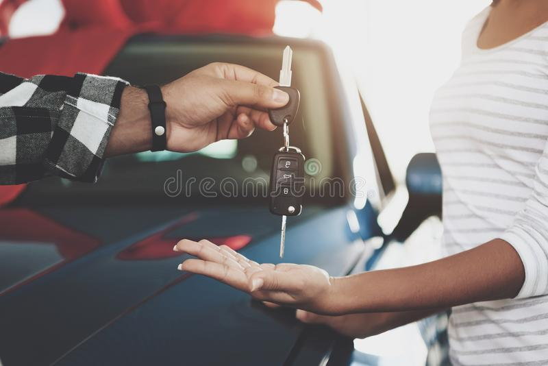Close up man is giving keys to woman. African american family at car dealership. Father, mother and son near new car. stock photo