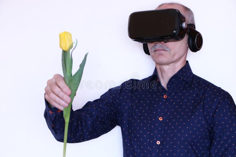 Close-up - a man with glasses of virtual reality gives a tulip stock images