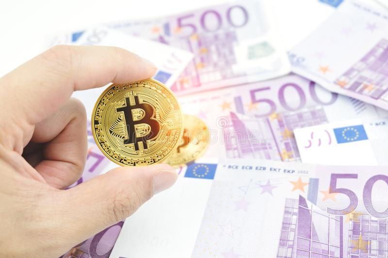 Close up man hand holding golden bitcoin over blurred five hundred euro banknotes background. royalty free stock photos
