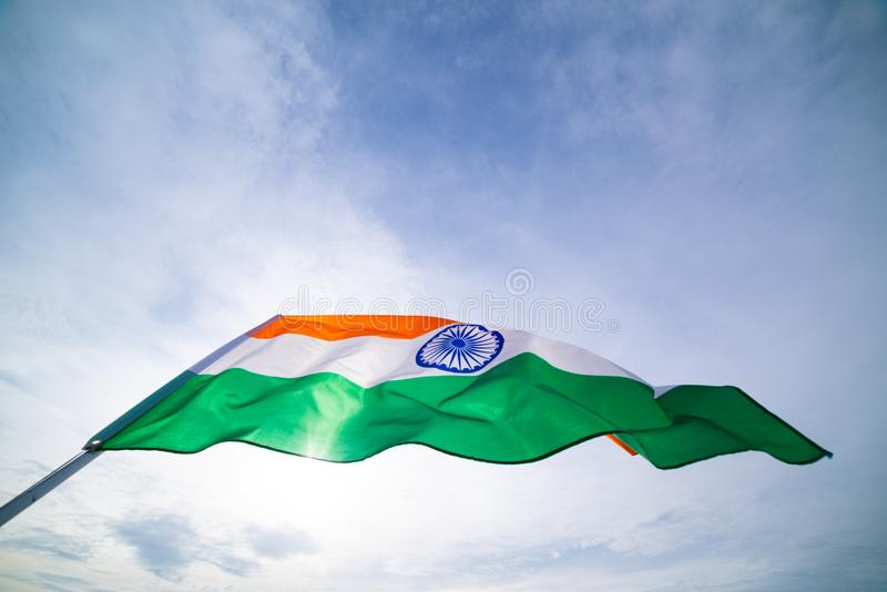 Close up man hand holding India flag on the blue sky background. Indian Independence Day, 15 August stock photography
