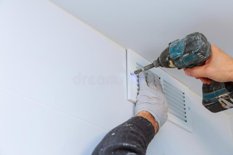 Close up man hand installing vent cover from ceiling. Mounted Air Conditioner ventilation home conditioning metal architecture technology panel wall interior royalty free stock images