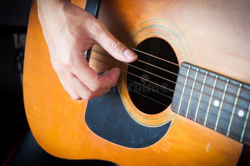 Close-up man handen die akoestische gitaar spelen stock afbeelding