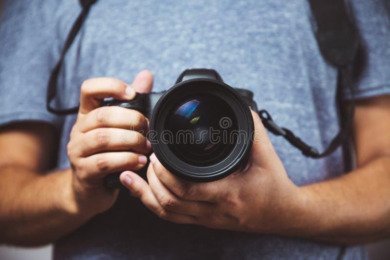 Close up of man hands holding DSLR Camera - Man photograph with camera stock image