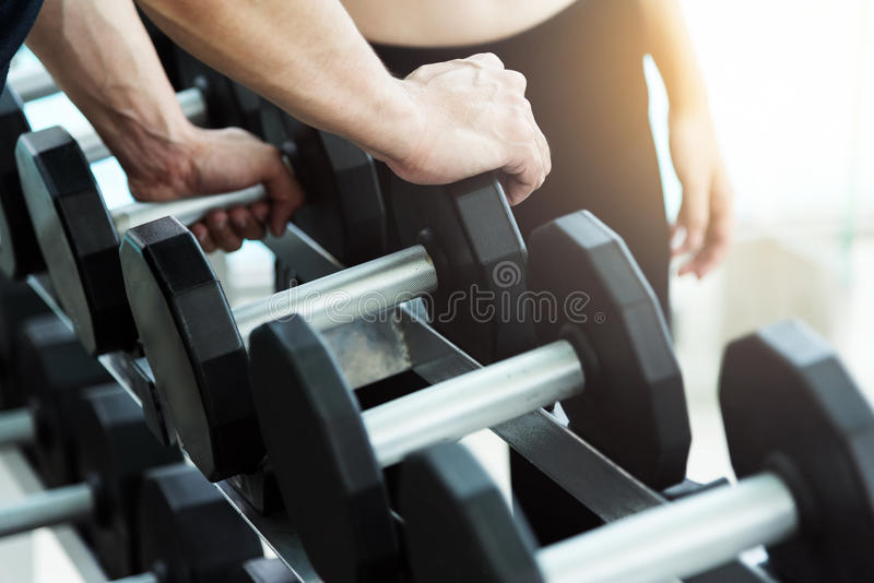 Close up man hands holding dumbbells stock images