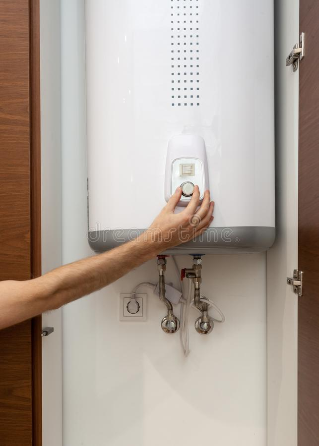 Close-up of man hands setting the temperature of water in Electric Boiler. stock photography