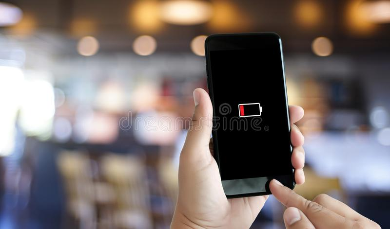 Close up man hands using smart phone battery low charged battery royalty free stock image