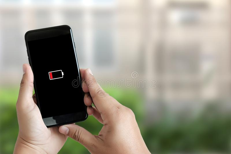 Close up man hands using smart phone battery low charged battery royalty free stock images
