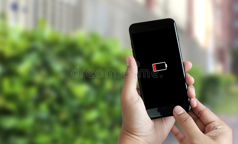 Close up man hands using smart phone battery low charged battery royalty free stock photo
