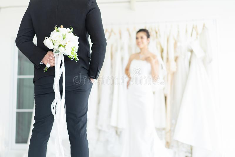Close up of man has prepared his roses to her surprise woman in wedding dress fitting room. Romantic date or wedding or valentines royalty free stock images
