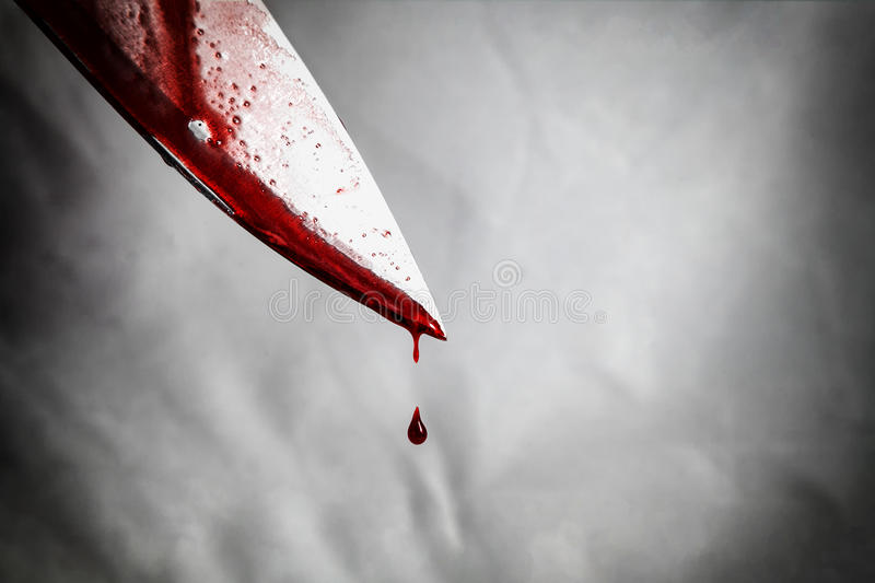 close-up of man holding knife smeared with blood and still dripping. stock image