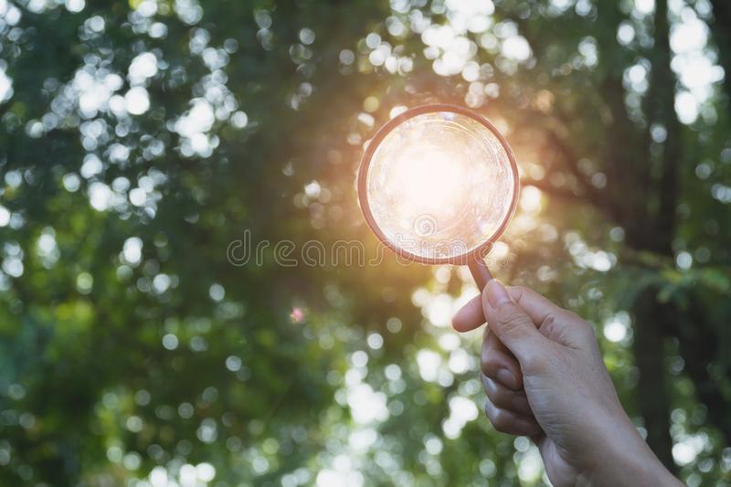 Close-up man holding magnifying glass for looking at the light o royalty free stock image