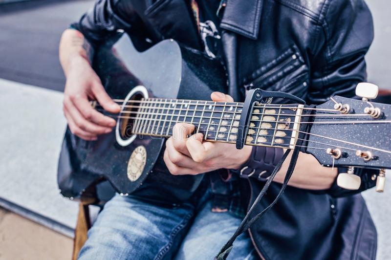 Close up of a man in a leather jacket playing an old black acoustic guitar royalty free stock photo