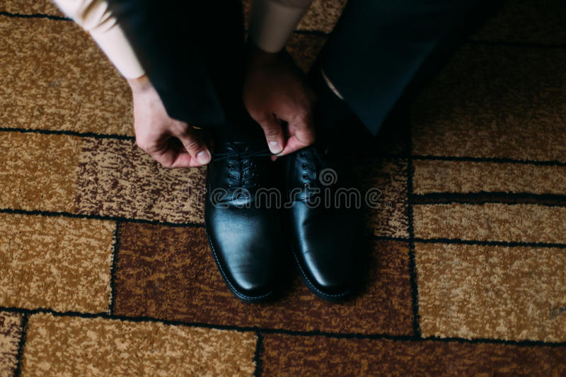 Close up of man leg and hands tying stylish black shoe laces standing on carpet with rectangular ornament stock image