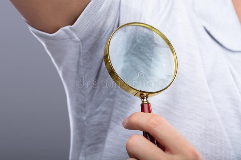 Man With Sweaty Armpit Holding Magnifying Glass royalty free stock photo