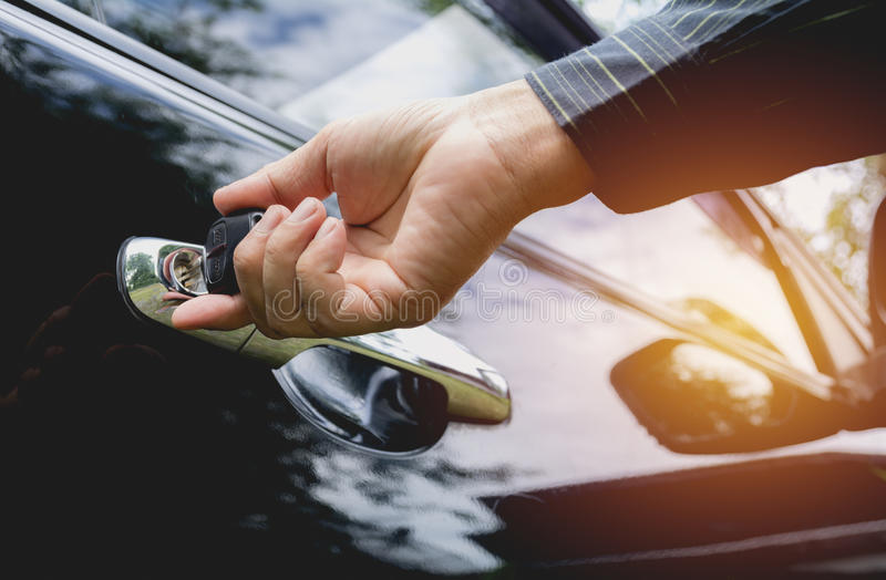 Close-up of man opening a car door. Hand on handle. stock photo