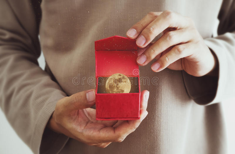Close-up a man opening red gift box, with the moon and stars inside, vintage tone royalty free stock image
