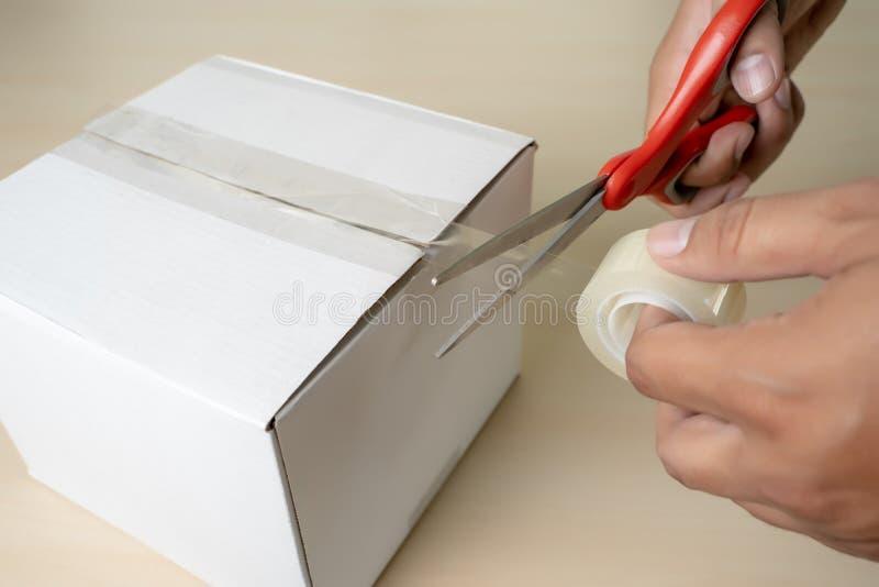 Close-up man packing box, adhesive tape indoors royalty free stock photography