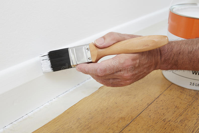 Close Up Of Man Painting Skirting Board. With Brush stock photo