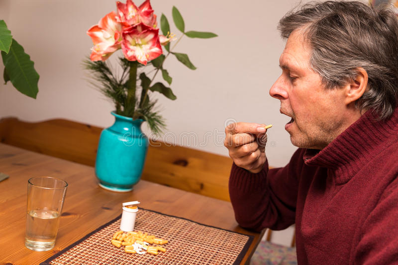Close up of a man with pills. Close up of a elderly man with pills stock image
