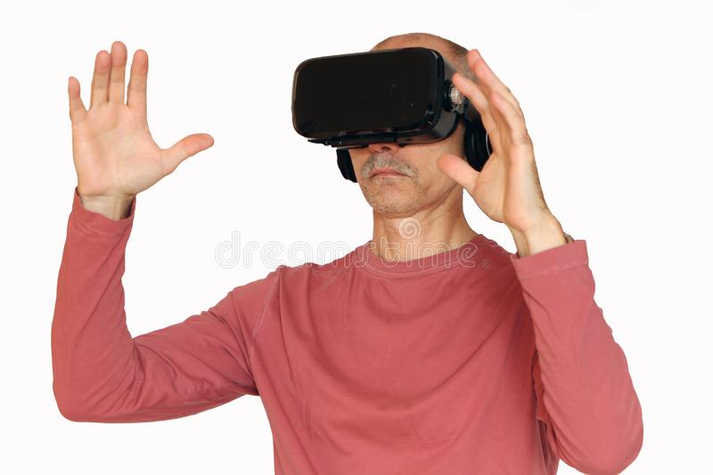 Close-up of a man in a pink T-shirt with glasses of virtual reality stock photo
