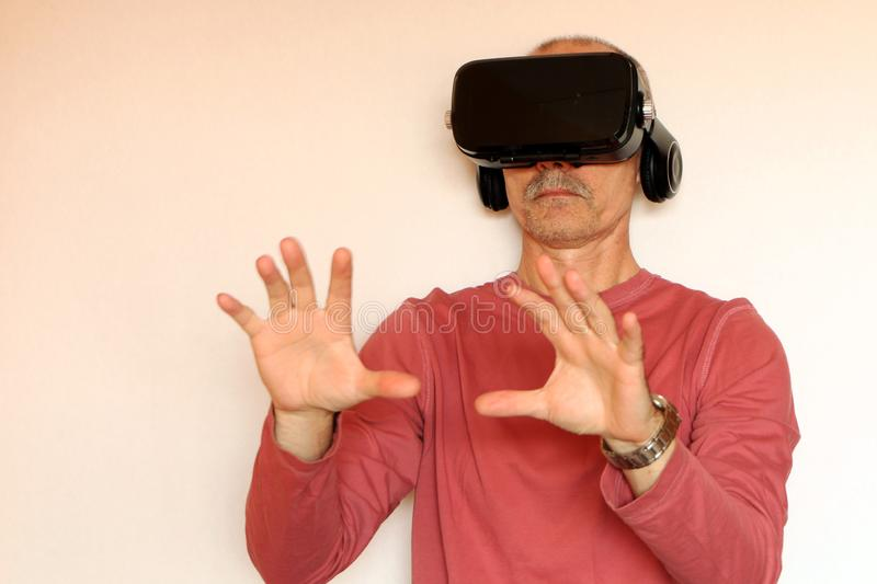 Close-up of a man in a pink T-shirt with glasses of virtual reality stock photos