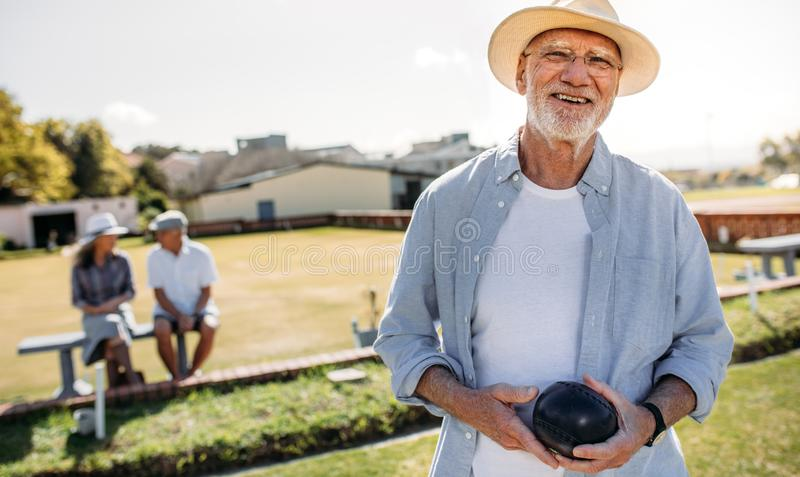 Close up of a man playing boules in a lawn stock photos