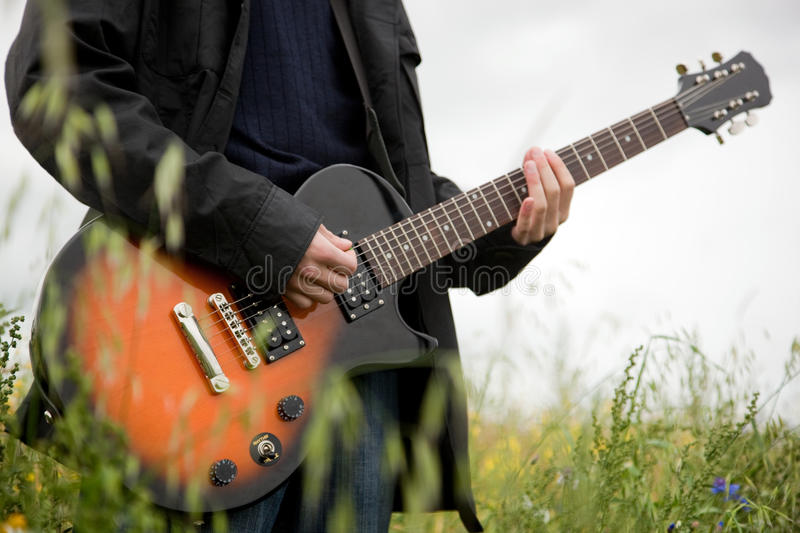 Close up of a man playing guitar. Outdoors stock photo