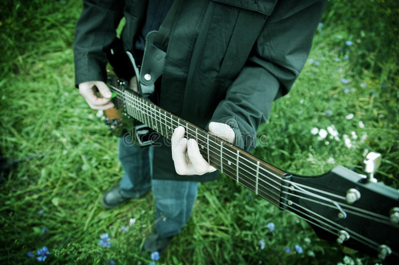 Close up of a man playing guitar. Outdoors stock photography