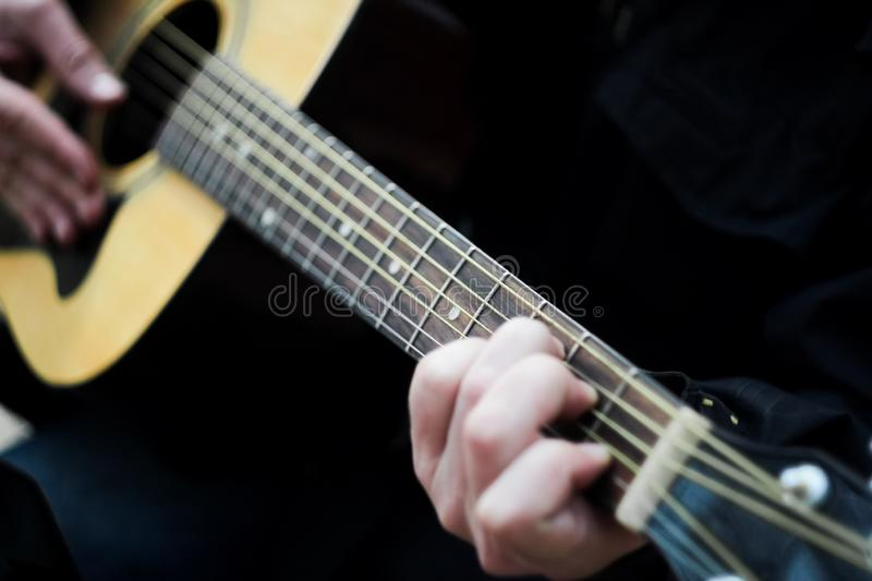 Close-up. A man playing a six-string acoustic guitar. Blurred stock photography