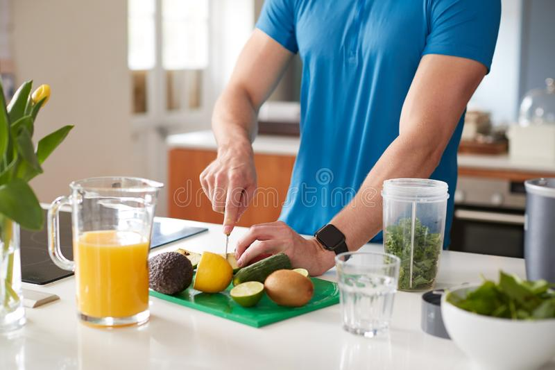Close Up Of Man Preparing Ingredients For Healthy Juice Drink After Exercise stock photo