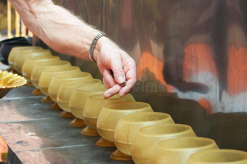 Man putting coins in monk`s alms bowl royalty free stock photo