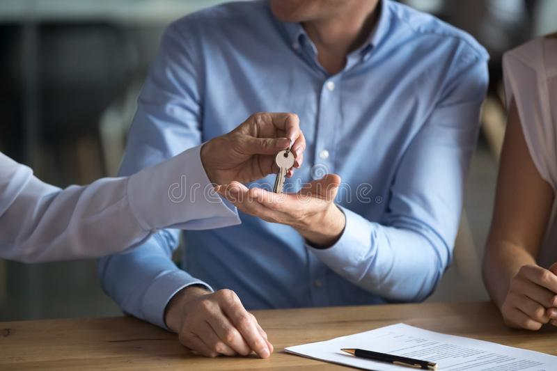 Close up man receiving keys from new house, making deal. Close up men receiving keys from new house, making deal with realtor in office, tenant signing lease royalty free stock images