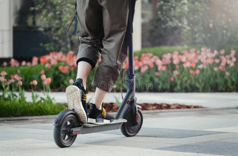 Close up of man riding black electric kick scooter at beautiful park landscape. Man is on foreground, modern building and park is on background stock photo