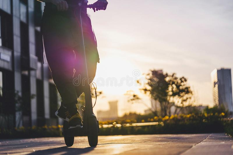 Close up of man riding black electric kick scooter at cityscape at sunset stock photography