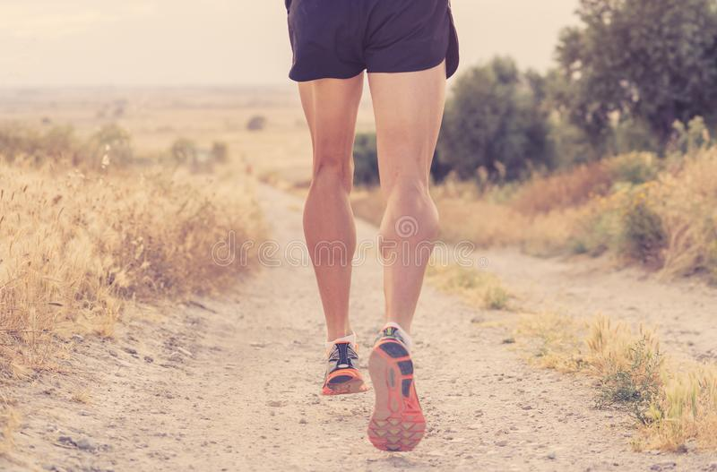 Close up of man running legs at sunset on a country road. royalty free stock images
