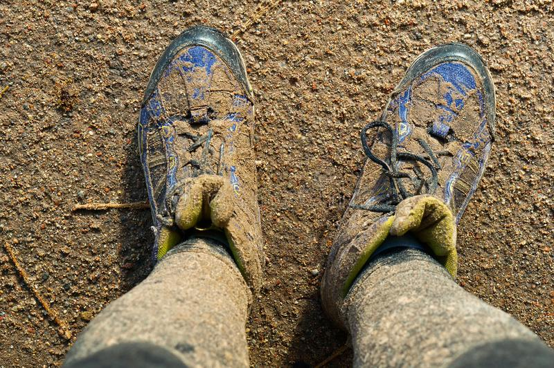 Close up of man`s boots while hiking on trail in the mountains royalty free stock image