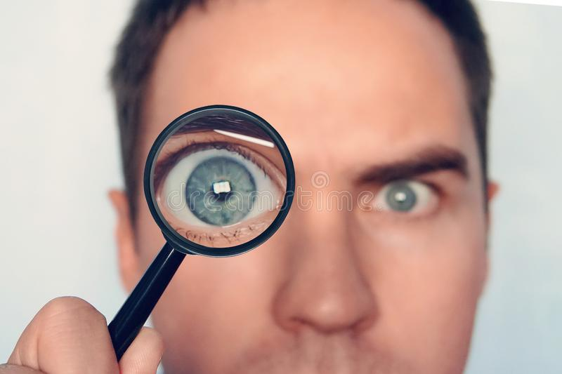 Close up of man`s face with the loupe close to one eye on white background. View to round human eye through the royalty free stock photography