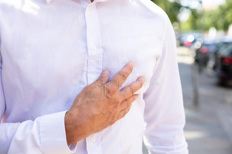 Man Suffering From Chest Pain. Close-up Of Man`s Hand On Chest At Outdoors stock images
