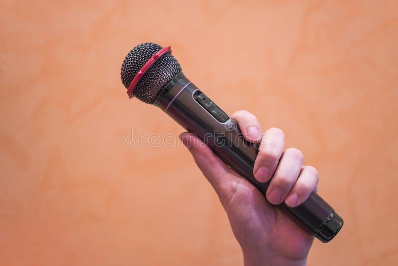 Close-up of a man`s hand holding a black microphone on an orange royalty free stock images