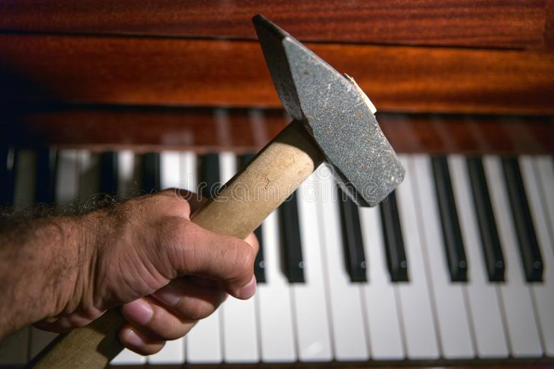 Heavy feelings about music. Close up of a man`s hand holding a heavy hammer approaching the keyboard of a classical piano royalty free stock photos