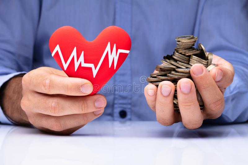 Man Holding Heart With Pulse Rate And Golden Coins royalty free stock photos