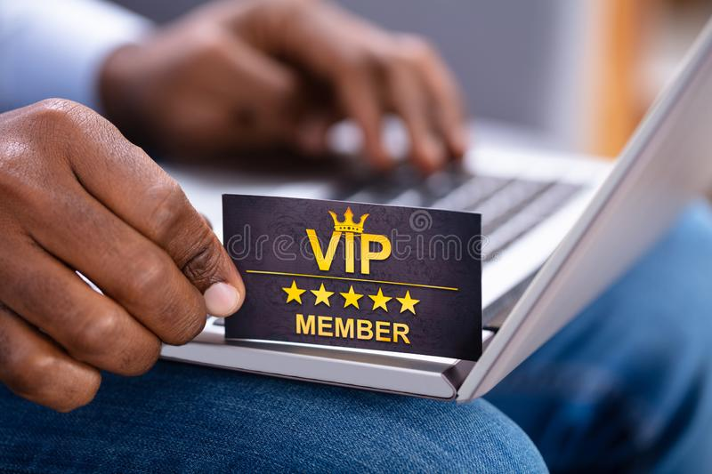 Close-up Of A Man`s Hand Holding VIP Member Card. While Using Laptop royalty free stock photography