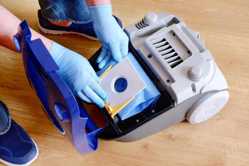 A man`s hand installing a clean empty dust bag in a vacuum cleaner royalty free stock photos
