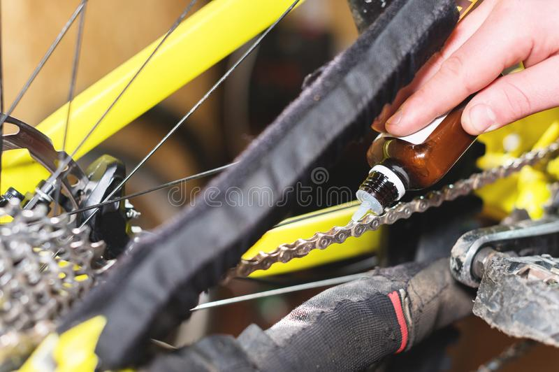 Close-up of a man`s hand, led by masters, lubricate the bicycle chain of a mountain bike with a special lubricant in the. Home workshop royalty free stock photo